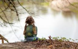 Petite seule fille sur la nature près de la rivière Photographie stock