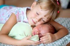 Petite soeur étreignant son frère nouveau-né Enfant d'enfant en bas âge rencontrant le nouvel enfant de mêmes parents  photos libres de droits