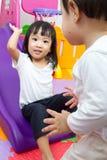 Petite soeur asiatique et frère chinois jouant sur la glissière Photos stock