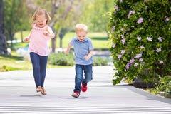 Petite soeur et frère doux Having Fun Running au parc Photographie stock libre de droits