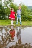 Petite soeur et frère jouant avec le papier Photos stock