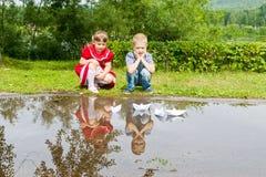 Petite soeur et frère jouant avec le papier Photographie stock libre de droits