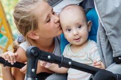 Petite soeur heureuse embrassant le frère de bébé Photo stock