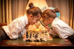 Petite soeur jouant des échecs et regardant l'oeil pour observer Images libres de droits