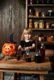 Petite sorcière dans un amusement noir de robe au sujet des articles magiques Photos libres de droits