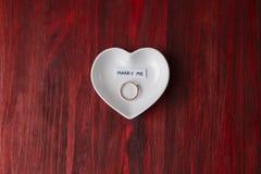 Petite soucoupe en céramique sous forme de coeur avec un anneau et une note photo stock