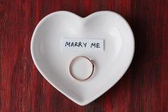 Petite soucoupe en céramique sous forme de coeur avec un anneau et une note images stock