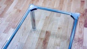 Petite table en verre claire contre le plancher en bois sur la réception de bureau Photos stock