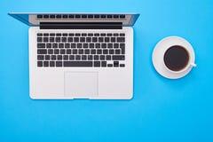 Petite tasse de café et un ordinateur portable argenté moderne se trouvant sur le bleu Image libre de droits