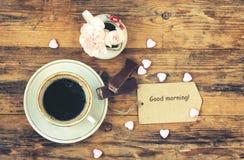 Petite tasse de café, oeillets roses, étiquette de papier Images stock
