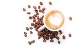 Petite tasse de cappuccino avec des grains de café Photos libres de droits