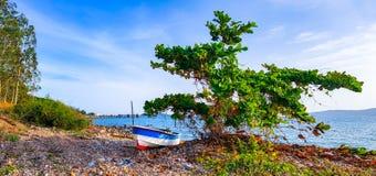 Petite utilisation de bateau de fibre de verre pour pêcher ou naviguer le sport sur la plage de roche image stock
