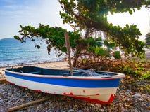 Petite utilisation de bateau de fibre de verre pour pêcher ou naviguer le sport sur la plage de roche photo stock