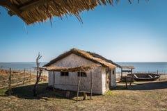 Petite vieille maison d'adobe, puits en bois et un bateau troué sur le bord de la mer photos stock