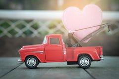 Petite voiture rouge de jouet et coeurs roses pour le jour du ` s de valentine Photos stock