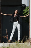 Petite young woman with very long hair wear heels and white pants Stock Image