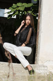 Petite young woman with very long hair wear heels and white pants Royalty Free Stock Image