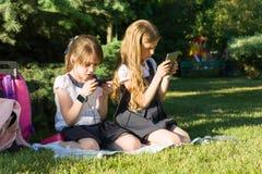 Petites écolières attirantes d'amies avec les sacs à dos, smartphones sur un pré en parc Photos libres de droits
