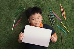 Petites 7 années mignonnes de dessin de garçon en parc en dehors du mensonge sur l'herbe photos libres de droits