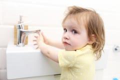 Petites 2 années mignonnes de mains de lavage de fille dans la salle de bains Photo libre de droits