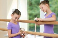 Petites ballerines heureuses tenant des chaussures de ballet Photos stock