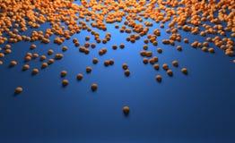 Petites boules oranges glissant le long de la surface bleue Image libre de droits