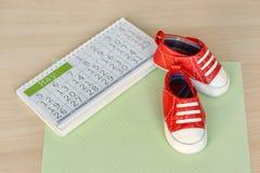 Petites chaussures de bébé avec le calendrier sur le fond en bois Photos libres de droits