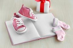 Petites chaussures de bébé, carnet, chaussettes et boîte actuelle sur le fond en bois Images libres de droits