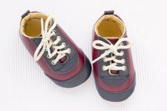Petites chaussures de bébé mignonnes sur le fond blanc Chaussures en cuir d'enfant Photographie stock libre de droits