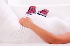 Petites chaussures pour le bébé à venir dans le ventre de la femme enceinte Photos libres de droits