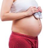 Petites chaussures pour le bébé à venir dans le ventre de la femme enceinte Image libre de droits