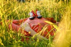 Petites chaussures pour le bébé à venir dans le ventre de la femme enceinte Femme enceinte tenant la petite détente de chaussures Photographie stock libre de droits