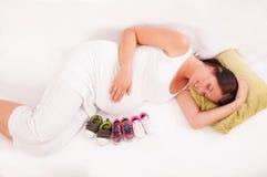 Petites chaussures vis-à-vis du ventre de W enceinte Images stock