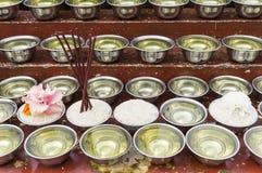 Petites cuvettes avec l'eau et le riz autour d'un temple Photos libres de droits