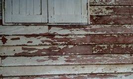 Petites fenêtres dans le mur d'une vieille maison en bois Photos stock