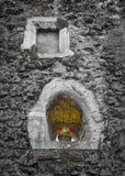 Petites fenêtres dans le mur de château Images stock