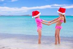 Petites filles adorables dans des chapeaux rouges de Santa sur la plage Images stock