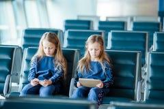 Petites filles adorables dans jouer de embarquement de attente d'aéroport avec l'ordinateur portable Image stock