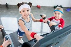 Petites filles adorables dans les vêtements de sport s'exerçant sur le tapis roulant et souriant à l'appareil-photo dans le gymna Image libre de droits