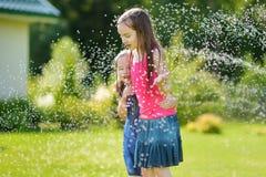 Petites filles adorables jouant avec une arroseuse dans une arrière-cour le jour ensoleillé d'été Enfants mignons ayant l'amuseme Image libre de droits