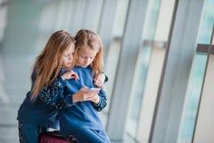 Petites filles adorables l'embarquement de attente d'aéroport et en jouant avec l'ordinateur portable Images stock