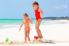 Petites filles adorables pendant des vacances d'été Les enfants jouant avec la plage joue sur la plage blanche Photo stock