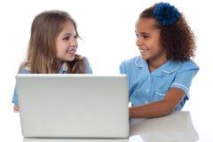 Petites filles apprenant dans l'ordinateur portable Photos stock