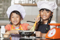 Petites filles asiatiques stiring la farine et l'oeuf de blé Photographie stock libre de droits
