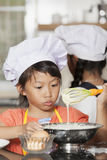 Petites filles asiatiques stiring la farine et l'oeuf de blé Images libres de droits