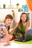Petites filles avec l'ordinateur à la maison Images stock