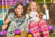 Petites filles balançant sur l'oscillation dans le terrain de jeu Photographie stock libre de droits