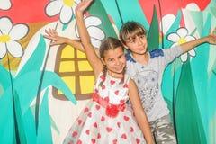 Petites filles balançant sur l'oscillation dans le terrain de jeu Photo stock