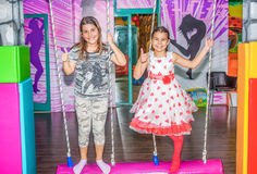 Petites filles balançant sur l'oscillation dans le terrain de jeu Photos stock