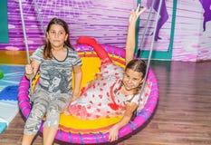 Petites filles balançant sur l'oscillation dans le terrain de jeu Image stock